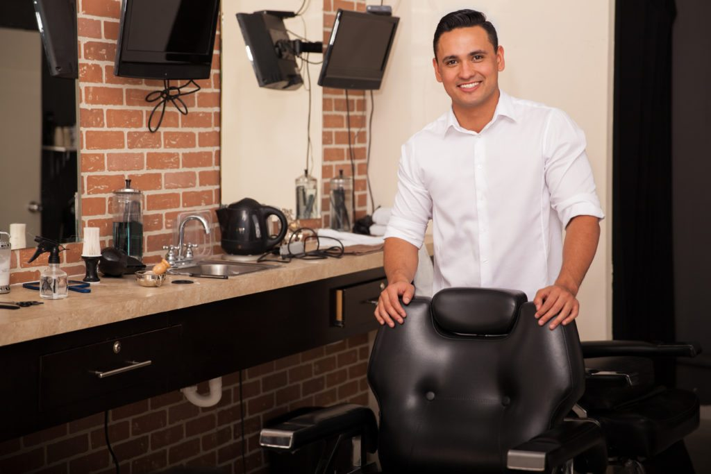 man standing behind chair in salon